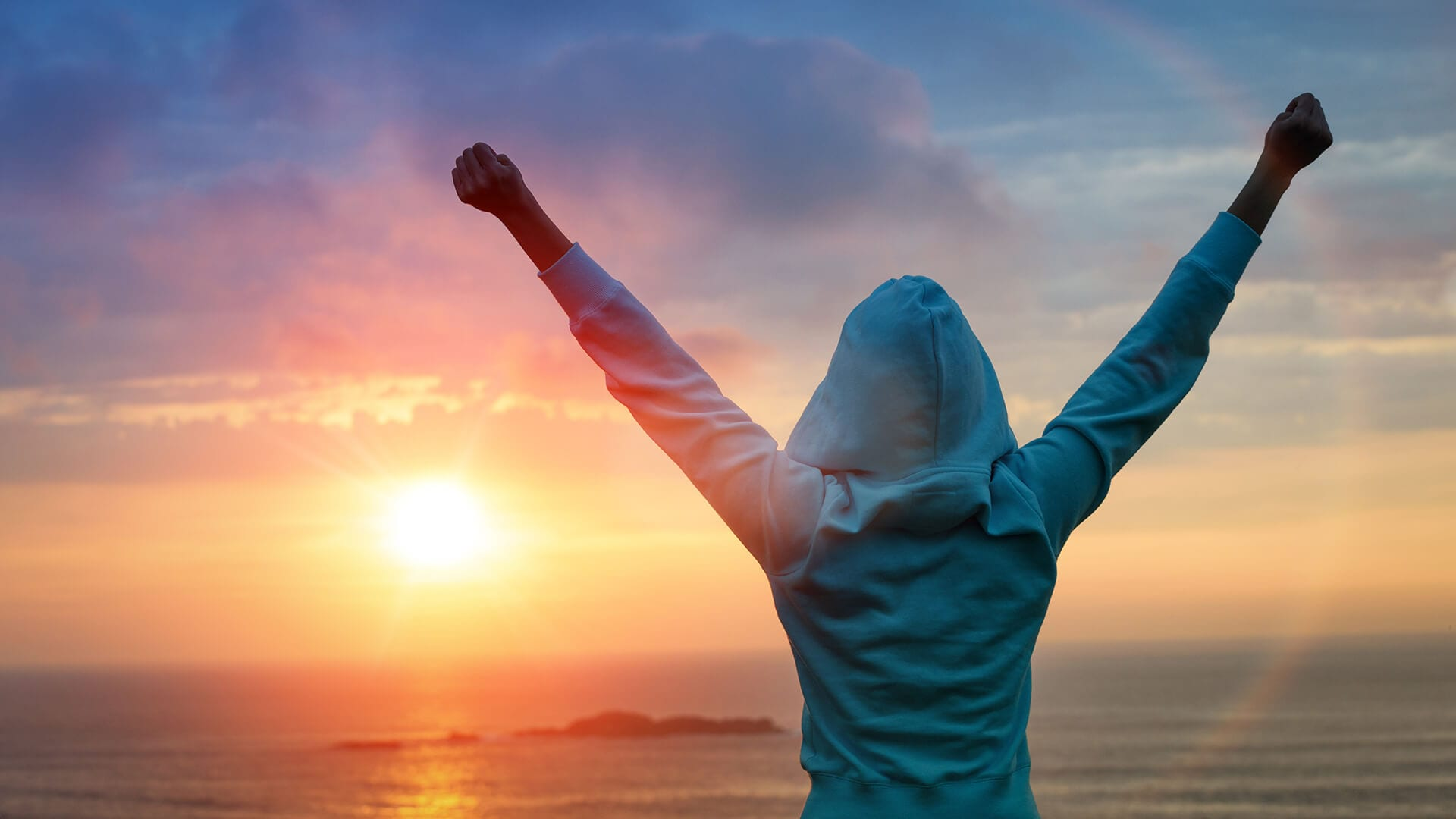 Hooded person with hands aloft in 'V' position with the sea and sun rising in the background.