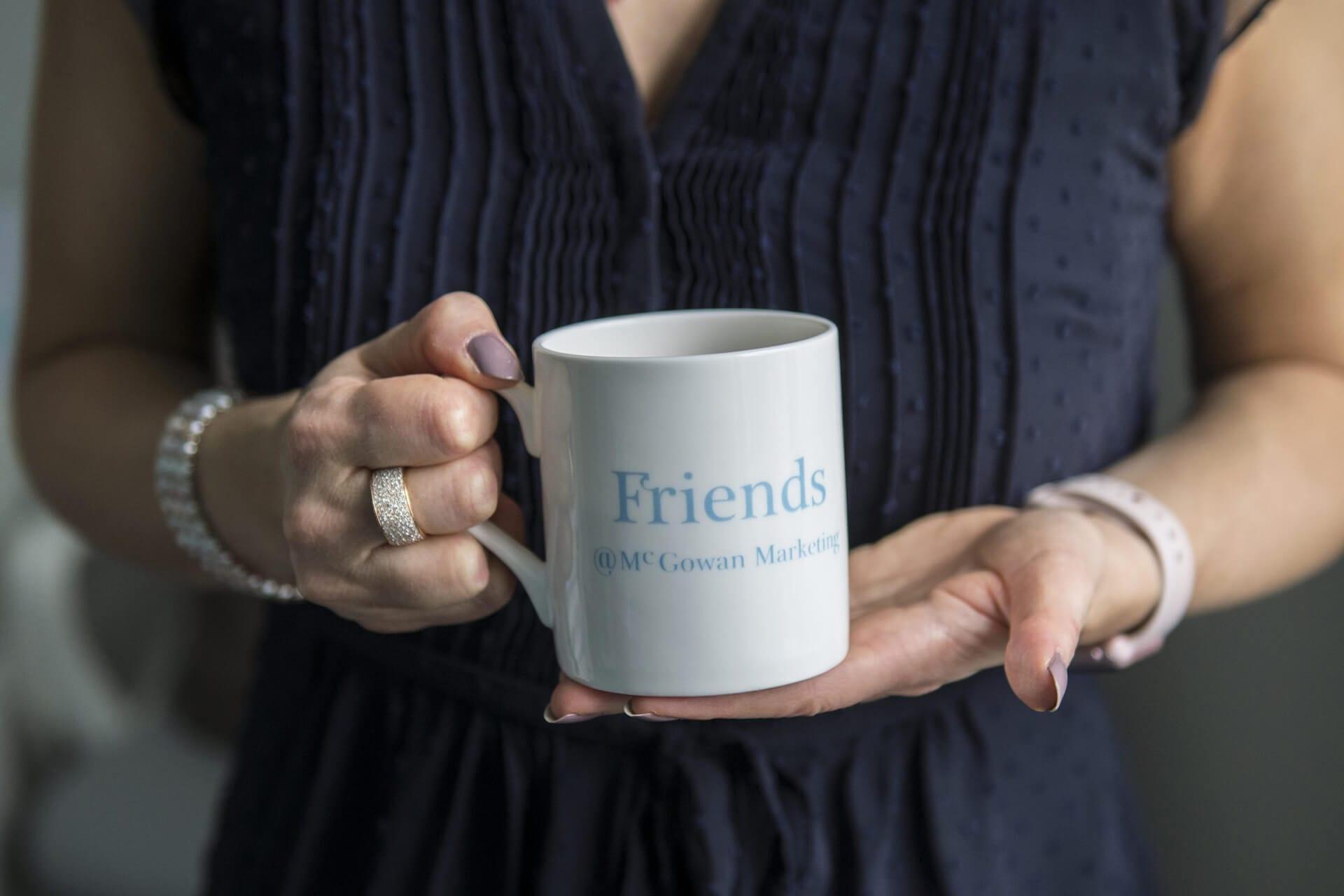 Emily McGowan of McGowan Marketing holding a mug.