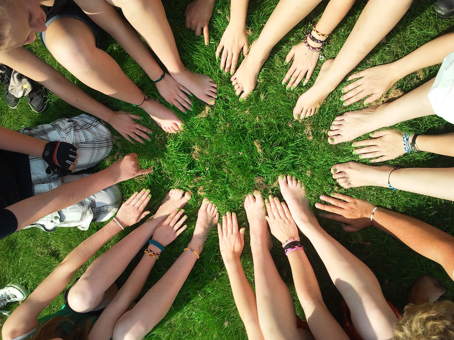 Top down view of various hands and bare feet with green nail varnish in a circle arrangement.