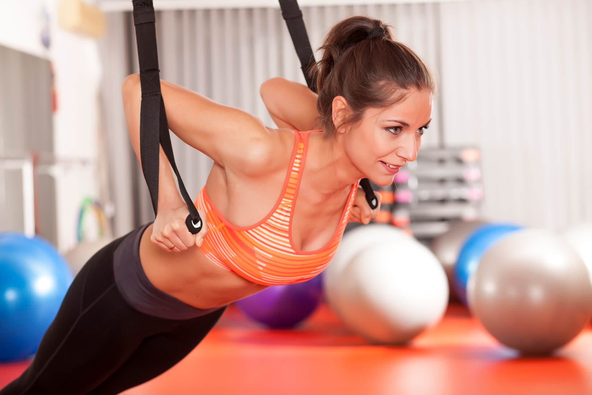 Female at a diagonal angle practising Pilates exercises with hanging band