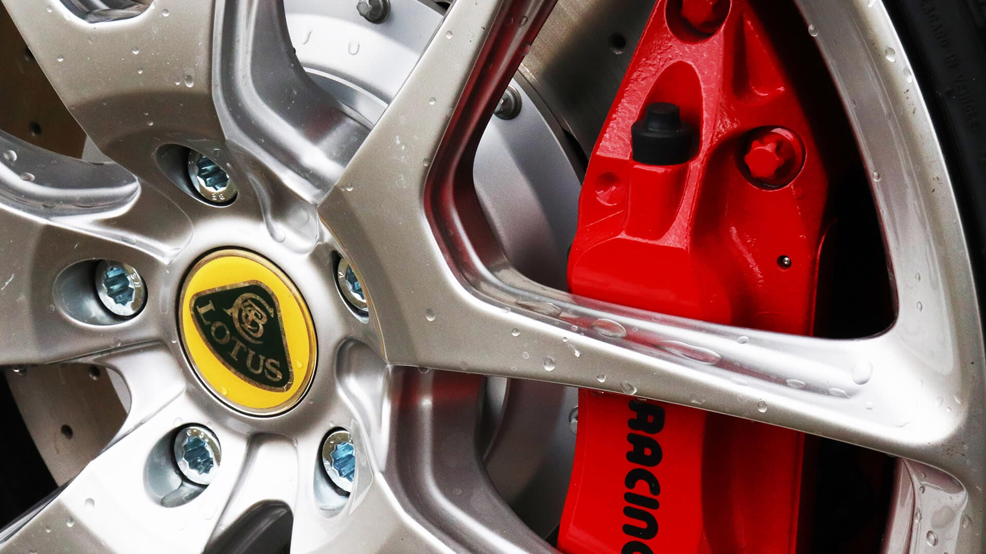 Close up view of a Lotus Evora alloy wheel with red caliper.