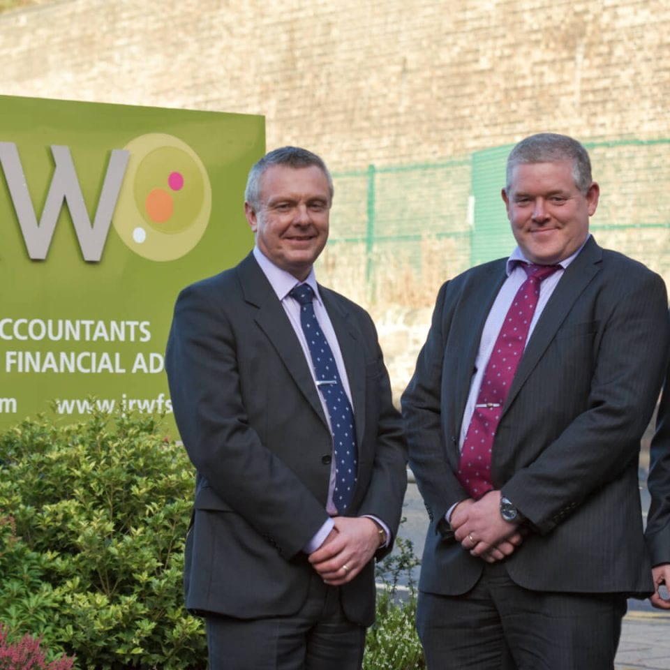JRW partners outside branded business sign in Galashiels