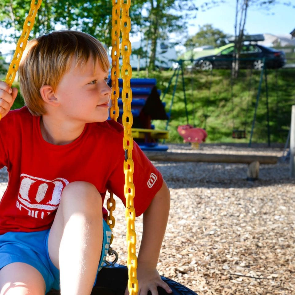Blond haired boy swinging on a tyre swing in a play park.