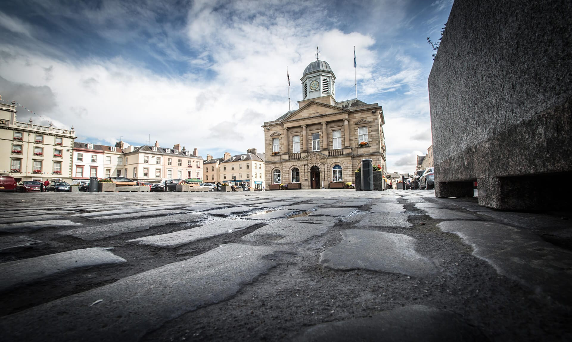 View of Kelso town hall from a very low angle showing cobbles in the foreground.