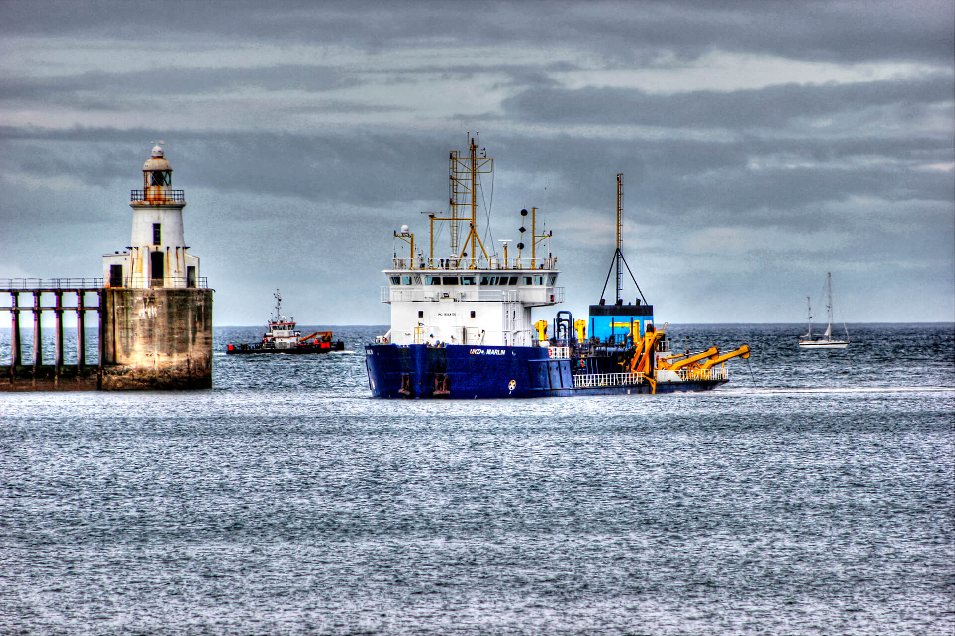 Blue hulled boat dredging near the lighthouse at the Port of Blyth, Northumberland