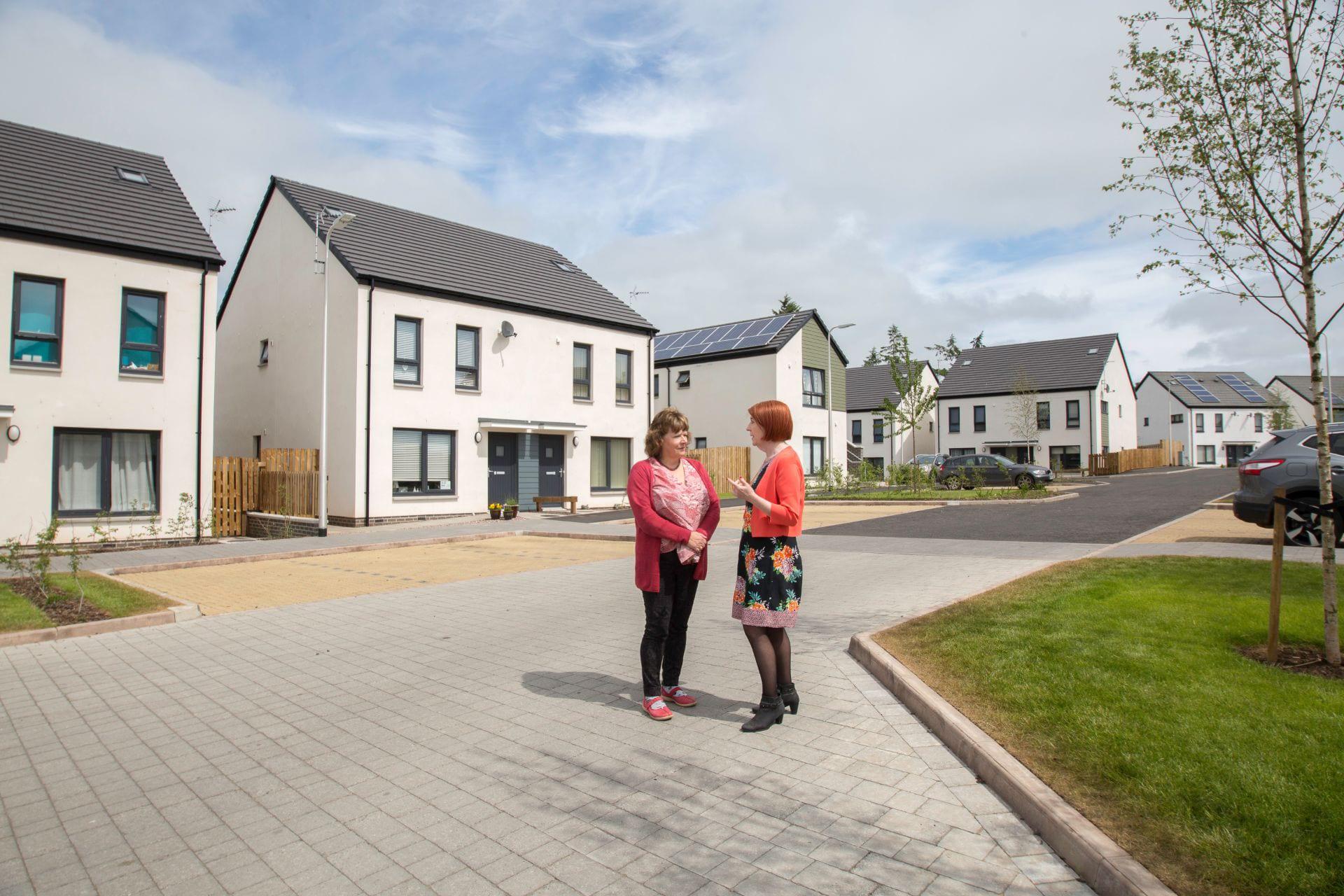 Two senior BHA staff standing in a housing development
